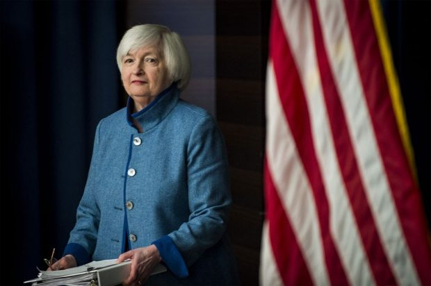 A photo of Janet Yellen standing in front of an American flag.