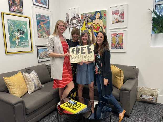 A photo of the staff of ShePlace holding a #FreeBritany sign