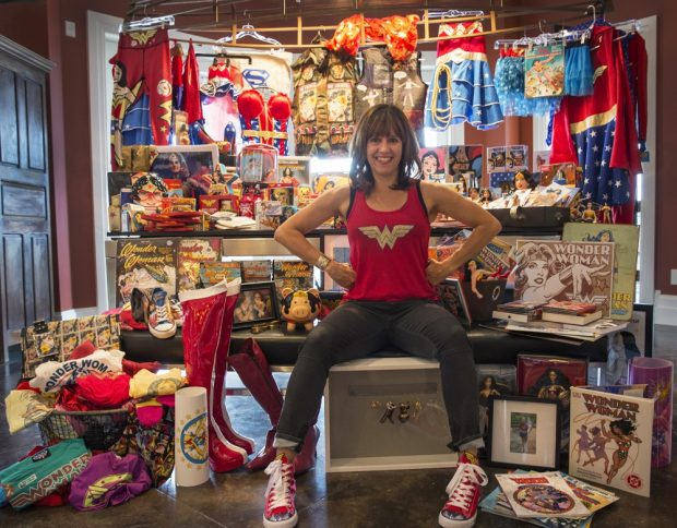 A photo of author Jacki Zehner sitting in front of a wall filled with Wonder Woman memorabilia.